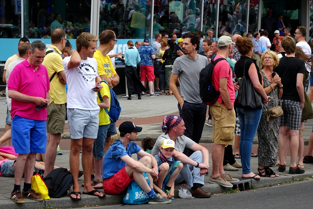 people sitting and waiting for Tour de France runners
