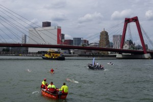 People in boats watching the swimmers under Willemsbrug